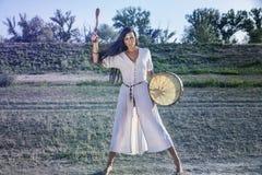 Shaman woman drumming. Shaman Pagan woman drumming alone Stock Photography
