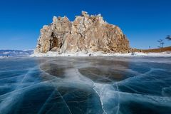 Shaman rock on frozen Baikal lake in winter,Russia. Shaman rock at Olkhon island in frozen Baikal lake with crack on surface and blue sky during winter,Siberia Stock Images