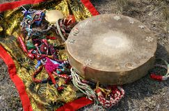 Shaman tambourine and mirror. Old shaman traditional accessories and belongings - ceremonial  tambourine, shawl and mirror. Tuva, Altay, Siberia, Mongolia Royalty Free Stock Photo