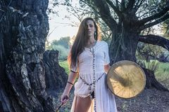 Shaman woman drumming. In the forest Royalty Free Stock Photo