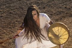 Shaman woman drumming. On the dirty road Royalty Free Stock Photos