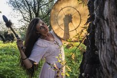 Shaman woman drumming. In the forest Stock Photo