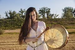 Shaman woman  drumming. On the road Royalty Free Stock Images