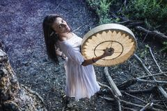 Shaman woman drumming. Under the tree Stock Images