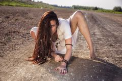 Shaman woman on the road crawling. Shaman woman on the road slowly crawling stock image