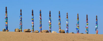 Shamanic pillars tied with colored ribbons Royalty Free Stock Image