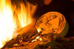 Shamanic tambourine in front of a bonfire
