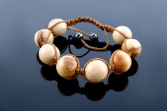 Shamballa bracelet made of wood on a black Stock Photos