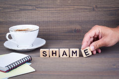 Shame. Wooden letters on dark background Stock Photo
