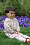 Shamefaced girl. Chinese girl sit in a garden Stock Photos