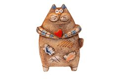 Shamot cat. Figurine (statuette) of a funny fat cat holding small red heart in its hands. Figurine is made of shamotte (fire clay) and has nice detailed natural Stock Image