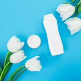 Shampoo bottle, cream and white tulips flowers on blue background. Beauty blog. Flat lay, top view. Shampoo bottle, cream and white tulips flowers on blue Royalty Free Stock Image