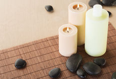 Shampoo bottle, massage stones and candles Stock Photo