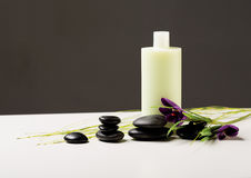 Shampoo bottle, massage stones and iris flower Stock Photography