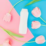 Shampoo bottle and tulips flowers on pink and blue background. Flat lay, top view. Shampoo bottle and tulips flowers on pink and blue background. Flat lay Stock Photos