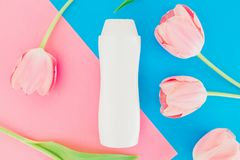 Shampoo bottle and tulips flowers on pink and blue background. Flat lay, top view. Shampoo bottle and tulips flowers on pink and blue background. Flat lay Stock Photography
