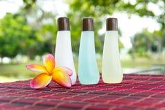 Shampoo bottles and yellow frangipani Royalty Free Stock Images