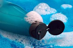 Shampoo Bubbles. Opened bottle of shampoo with soap bubbles and water droplets on a shiny watery blue background Royalty Free Stock Images