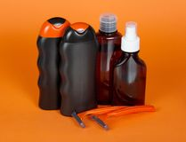 Shampoo, gel, lotion and safety razor. On an orange background royalty free stock photo