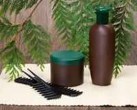 Natural hair care cosmetics. Shampoo, hair mask and combs against the background of fresh green plant branches. Natural hair care cosmetics royalty free stock photography