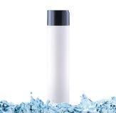 Shampoo mit befeuchtendem Effekt in der weißen Flasche mit Kopienraum im Wasserspritzen Lizenzfreie Stockfotos