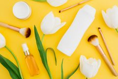 Shampoo, perfume, cream and white tulips flowers on yellow background. Beauty composition. Flat lay, top view. Shampoo, perfume, cream and white tulips flowers Royalty Free Stock Photo
