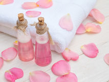 Shampoo in the small bottles, white towel and rose petals Royalty Free Stock Images