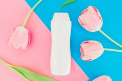 Shampoo and tulips flowers on pink and blue background. Flat lay, top view. Shampoo and tulips flowers on pink and blue background. Flat lay Royalty Free Stock Image