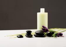 Shampooflasche, Massagesteine und Iris blüht Stockfotografie