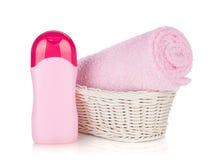 Shampooflaska och rosa handduk Fotografering för Bildbyråer