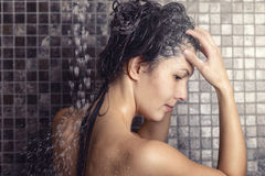shampooing她长的棕色头发的妇女 免版税库存图片