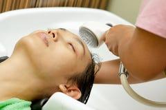 Shampooing et lavage de cheveu au salon de coiffure images libres de droits
