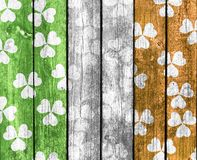 Shamrock background. Vertical boards with an overlay of shamrocks in green, white and orange representing the flag of Ireland, in a St. Patrick's Day theme Stock Images