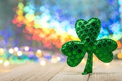 Shamrock and bright rainbow background and soft bokeh lights on wooden board. Rainbow background on wooden board, selective focus, shallow DOF. For St. Patrick`s royalty free stock photos