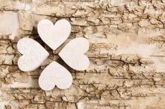 Shamrock (clover) made of wooden hearts on bark background. Stock Image