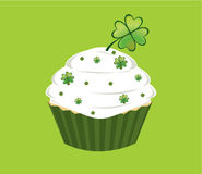 Shamrock cupcake. Cupcake decorated with green diamond shapes and shamrocks on white frosted in front of a white background royalty free illustration