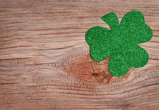 Shamrock over old wood background. Glitter Green Clover. Stock Photography