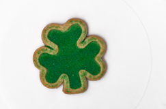 A  shamrock shaped cookie on a white plate Royalty Free Stock Image