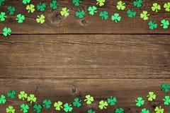 Shamrocks дня St Patricks удваивают границу над деревенской древесиной Стоковая Фотография