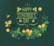 Shamrocks and coins with happy st patricks day lettering. Top view of shamrocks and coins with happy st patricks day lettering stock image