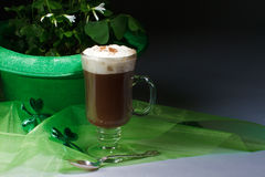 Shamrocks and Irish coffee on dark. Glass of Irish coffee topped with whipped cream and cinnamon, next to green bowler hat filled with shamrocks. Sheer green royalty free stock photography