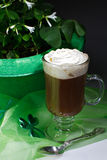 Shamrocks and Irish coffee dark vertical. Glass of Irish coffee topped with whipped cream and cinnamon, next to green bowler hat filled with shamrocks. Sheer stock photos