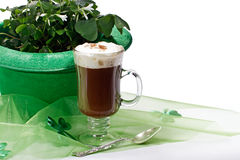 Shamrocks and Irish coffee on white. Glass of Irish coffee topped with whipped cream and cinnamon, next to green bowler hat filled with shamrocks. Sheer green stock images