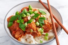 Shan noodles with chopsticks at white marble tabletop. burmese cuisine traditional dish. myanmar food. Rice noodles with pork in tomatos. asian dish royalty free stock image