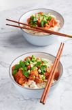 Shan noodles with chopsticks at white marble tabletop. burmese cuisine traditional dish. myanmar food. Rice noodles with pork in tomatos. asian dish stock image