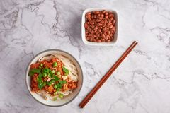 Shan noodles with peanuts and chopsticks at white marble tabletop. burmese cuisine traditional dish. Myanmar food. rice noodles with pork in tomatos stock photography
