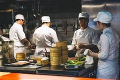 Shangai, China - 27 de mayo de 2019: Los cocineros chinos trabajan en la cocina del restaurante foto de archivo
