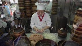Shangai, China - 11 de septiembre de 2013: el vídeo de los cocineros que hacían las bolas de masa hervida de Shangai, también lla almacen de video