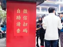 SHANGHAI, CHINA - Dec 21, 2018: de gelovigen kunnen wierook in de tempel van Shanghai Jingan door wechat kopen stock foto