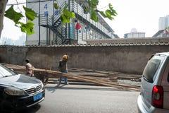 SHANGHAI, CHINA - em junho de 2018: Trabalhador da construção chinês que limpa o suor com o braço, pessoa isolada fotografia de stock royalty free